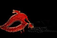 Maschera rossa e perle nere immagine stock