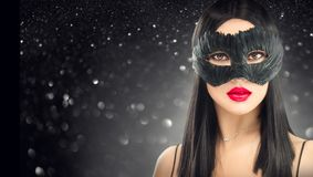 Maschera scura d'uso di carnevale della donna castana di fascino di bellezza, partito sopra il fondo del nero di festa fotografie stock