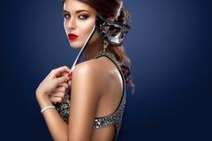 Maschera veneziana d'uso di carnevale di travestimento della donna di modello di bellezza al partito sopra il fondo di buio di fe fotografia stock libera da diritti