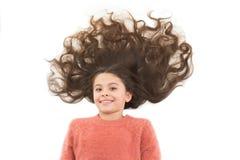 Maschere casalinghe naturali dei capelli che vi danno i bei capelli sani Bambino sveglio della ragazza con capelli ricci lunghi i immagine stock