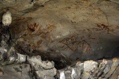 Maschere sulla parete della caverna Fotografia Stock