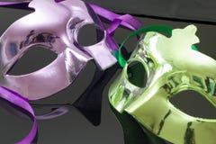 Mascherina viola e verde su priorità bassa nera Fotografia Stock