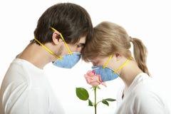 Mascherine da portare delle giovani coppie affettuose Fotografie Stock