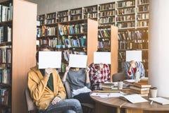 Maschi e ragazze che coprono i fronti in athenaeum fotografia stock libera da diritti