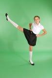 Maschiaccio grazioso della ragazza della scuola che solleva la sua gamba Fotografia Stock