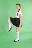 Maschiaccio grazioso della ragazza della scuola che solleva la sua gamba Fotografie Stock