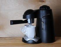 Maschine des schwarzen Kaffees mit zwei weißen Schalen auf einem hölzernen Hintergrund Lizenzfreies Stockfoto