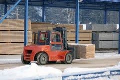 Maschine hebt Bauholz auf einer hölzernen Fabrik an stockfoto
