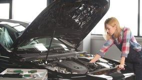 Maschinen neigen Überwachung Nette Blondine, die lernt, das Auto zu reparieren stock footage
