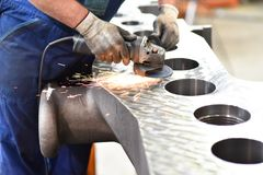 Maschinenbauarbeitskraft reibt Metall mit Maschine während c lizenzfreies stockbild