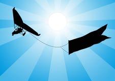 Maschinenhängegleiter mit einem Zeichen im Himmel gegenüber von der Sonne Lizenzfreie Stockbilder