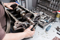 Maschinenkurbelwelle, Ventildeckel, Kolben Mechanikerschlosser bei der Automobilautomotorwartungsreparaturarbeit Lizenzfreie Stockfotografie