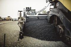 Maschinerie, die frischen Asphalt oder Bitumen während des Straßenbaus auf Baustelle legt Weinlese, Retro- Effekt auf Foto Stockbilder