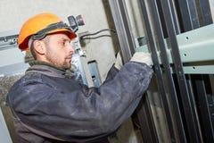 Maschinist mit dem Schlüssel, der Aufzugmechanismus in der Aufzugswelle justiert Lizenzfreie Stockfotografie