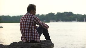 Maschio adulto deprimente che si siede sulla riva del fiume e che pensa al divorzio, solitudine video d archivio
