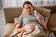 Maschio adulto stanco che fa male e che si trova a letto Fotografia Stock