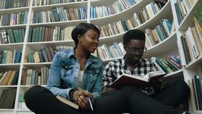 Maschio africano e libro di lettura delle studentesse, preparante agli esami mentre sedendosi sul pavimento vicino agli scaffali  stock footage