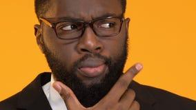Maschio afroamericano astuto che pensa alla decisione, scegliente fra le opzioni stock footage