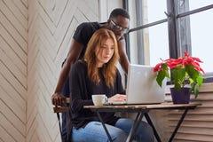 Maschio afroamericano e lavoro femminile caucasico con un computer portatile Fotografie Stock