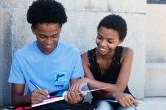 Maschio afroamericano e studentessa che preparano per l'esame Fotografie Stock Libere da Diritti