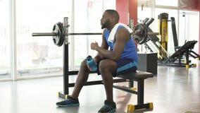 Maschio afroamericano stanco che si siede sull'attrezzatura di addestramento dopo l'allenamento attivo archivi video