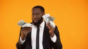 Maschio afroamericano in vestito convenzionale che fa i movimenti ballanti con i contanti del dollaro stock footage
