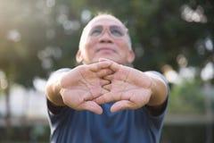 Maschio anziano asiatico che allunga prima dell'esercizio Immagini Stock Libere da Diritti