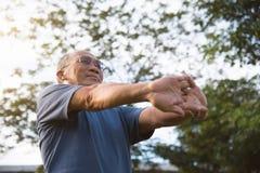 Maschio anziano asiatico che allunga prima dell'esercizio Fotografie Stock