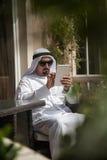 Maschio arabo facendo uso dello Smart Phone fuori Immagine Stock
