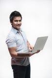 Maschio asiatico che tiene un computer portatile Fotografia Stock Libera da Diritti