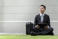 Maschio asiatico di affari facendo uso del computer portatile sul parco della città Fotografie Stock