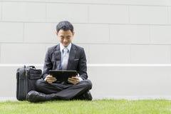 Maschio asiatico di affari facendo uso del computer portatile sul parco della città Fotografie Stock Libere da Diritti
