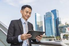 Maschio asiatico di affari facendo uso del computer portatile sulla città Immagini Stock