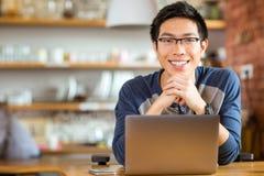 Maschio asiatico positivo in vetri con il computer portatile Immagini Stock Libere da Diritti