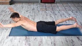 Maschio atletico che si trova sull'esercizio di pratica di yoga dello stomaco che gode dell'angolo alto sano di stile di vita video d archivio