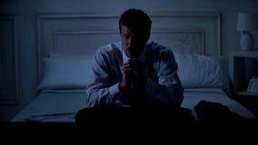 Maschio bello ansioso in vestito che si siede sul letto, mani di lucidatura, problemi fotografie stock
