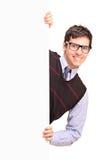 Maschio bello sorridente che propone dietro un comitato in bianco Fotografia Stock
