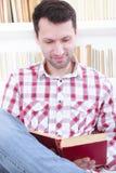 Maschio casuale che legge un libro mentre sta sedendosi sullo strato in Li Fotografia Stock
