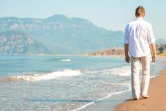 Maschio che cammina a piedi nudi sulla spiaggia Immagine Stock