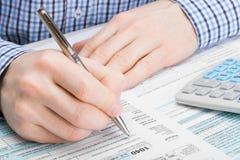 Maschio che compila la forma di imposta dei 1040 Stati Uniti d'America Immagine Stock