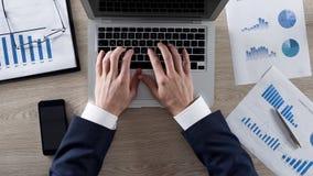 Maschio che digita i dati analizzati dei grafici sul computer portatile all'ufficio, visualizzazione superiore fotografia stock