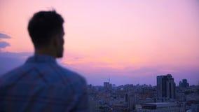 Maschio che esamina megalopoli dal tetto di costruzione, godente della vista maestosa fotografie stock