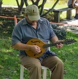 Maschio che gioca un mandolino alla secondi musica e Art Festival annuali immagine stock