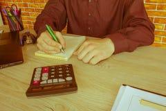 Maschio che lavora con il calcolatore, il documento di affari ed il taccuino del computer portatile Immagini Stock