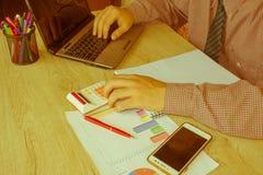 Maschio che lavora con il calcolatore, il documento di affari ed il taccuino del computer portatile Fotografie Stock Libere da Diritti
