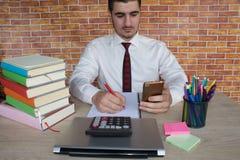 Maschio che lavora con il calcolatore, il documento di affari ed il taccuino del computer portatile Fotografia Stock Libera da Diritti