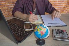 Maschio che lavora con il calcolatore, il documento di affari ed il taccuino del computer portatile Immagine Stock