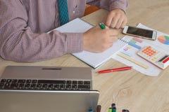 Maschio che lavora con il calcolatore, il documento di affari ed il taccuino del computer portatile Fotografia Stock