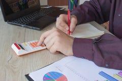 Maschio che lavora con il calcolatore, il documento di affari ed il taccuino del computer portatile Immagine Stock Libera da Diritti