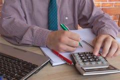 Maschio che lavora con il calcolatore, il documento di affari ed il taccuino del computer portatile Immagini Stock Libere da Diritti